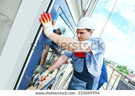Two builders worker installing glass windows on facade of business building using glass suction plates - stock photo