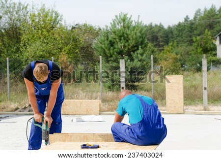 Two builders working on a building site using an electric drill on a wooden insulated wall panel - stock photo