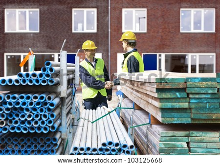 Two building contractors shaking hands behind stacks of scaffolding material, in front of a newly completed residential building complex - stock photo