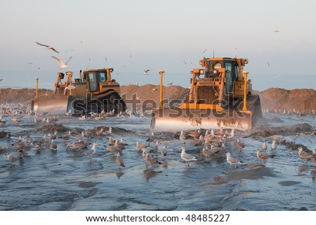 Two Bulldozers the beach on a dredging project in holland - stock photo