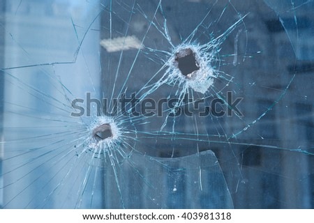 two bullet holes in the glass windows - stock photo