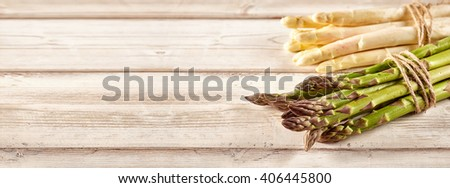 Two bundles of raw green white asparagus tied with brown loose string over wooden plank background - stock photo