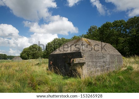 Two bunkers in nature with trees and grass with a cloudy blue sky