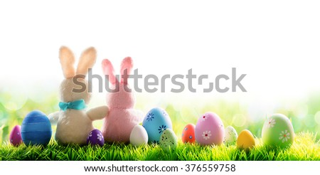 Two Bunnies With Decorated Eggs Isolated On Sunny Meadow - Easter Holiday Border  - stock photo