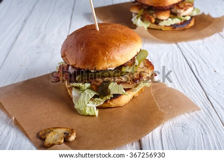 Two burgers with chicken breast, cheese sauce and mushrooms on wood background - stock photo