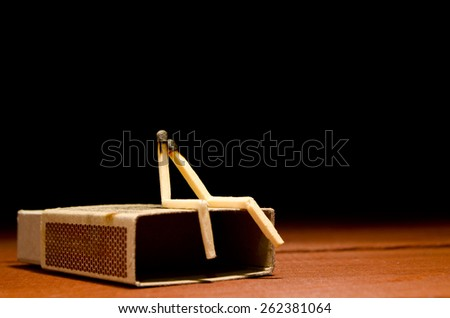 Two burned match humans sitting on a matchbox on a dark background - stock photo