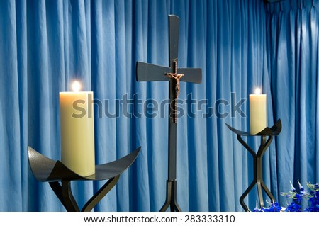 Two burning candles and a cross in a mortuary - stock photo