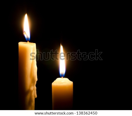 Two burning candles on a black background - stock photo