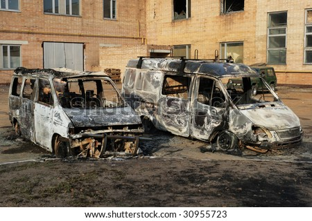 Two burnt down motor vehicles against a city landscape - stock photo