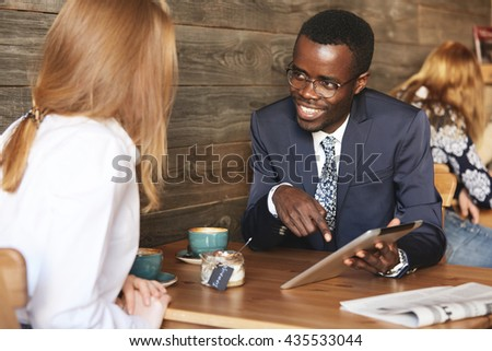 Two business associates of different races having meeting at a cafe: young African man in formal suit and glasses showing a presentation to his redhead Caucasian female colleague on digital tablet - stock photo