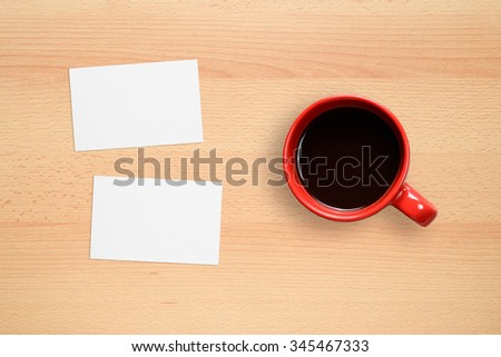 Two business cards and coffee cup on office desk