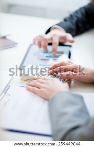 Two business colleagues, a man and woman, comparing and checking statistical business graph and data on a tablet computer as they sit side by side at the desk. - stock photo