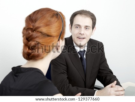 Two business colleagues, a man and woman, having a discussion with the man speaking while facing the camera - stock photo