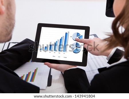 Two business colleagues discussing graph on digital tablet - stock photo