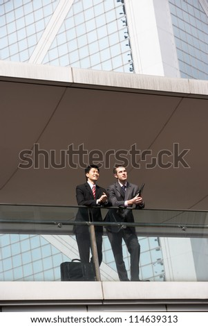 Two Business Colleagues Having Discussion Outside Office Building