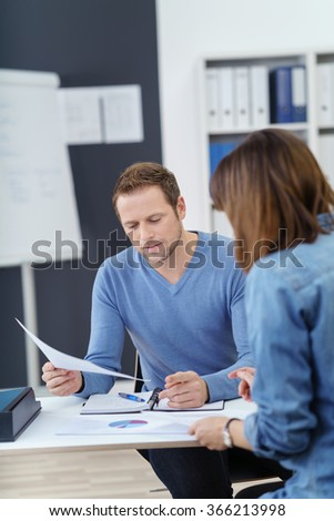 Two business colleagues in a meeting sitting at a desk in the office discussing paperwork with a serious expression, focus to a handsome young man - stock photo