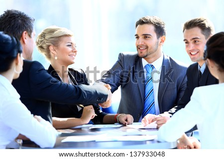Two business colleagues shaking hands during meeting - stock photo