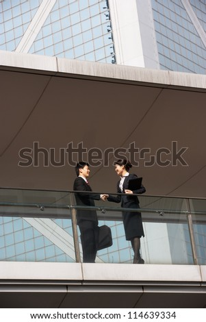 Two Business Colleagues Shaking Hands Outside Office Building - stock photo