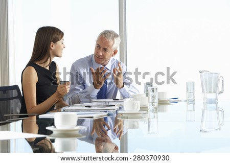 Two Business Colleagues Sitting Around Boardroom Table Having Informal Discussion - stock photo