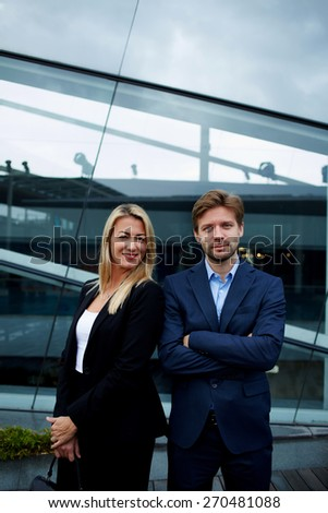 Two business colleagues standing against office building with brightly smile, experienced businessman standing with his female colleague smiling and looking to you, teamwork concept - stock photo