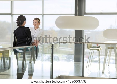 Two business colleagues standing in a modern office building hallway on a coffee break - stock photo