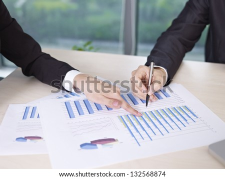 two business executives analyzing business performance in office. - stock photo