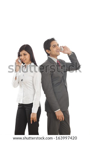 Two business executives talking on mobile phones - stock photo