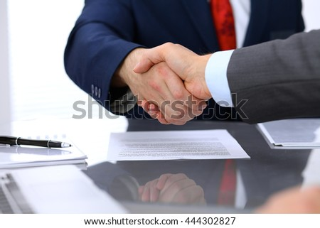 Two business man shaking hands to each other above signed contract