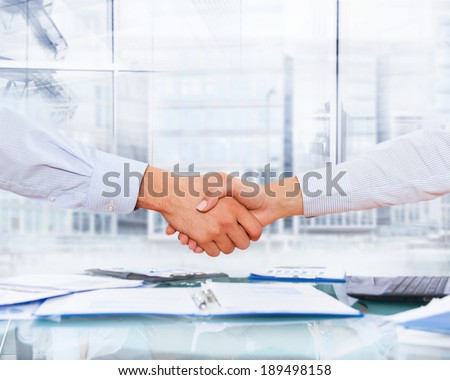 two business men and woman shaking hands, close businesspeople handshake after sign up documents contract, modern office desk over window city buildings - stock photo