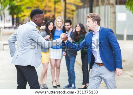 Two business men compete in arm wrestling with some colleagues inciting them. They are a black man and a caucasian one wearing smart casual clothes. Challenge and competition concepts.