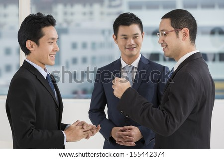 Two business men exchanging business cards. Caucasian and asian business men swapping business cards - stock photo