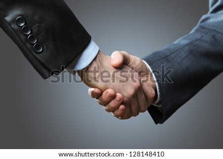 Two business men shaking hands, close up - stock photo