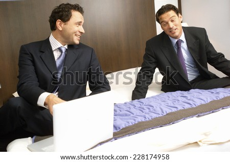 Two business men using laptop in hotel room