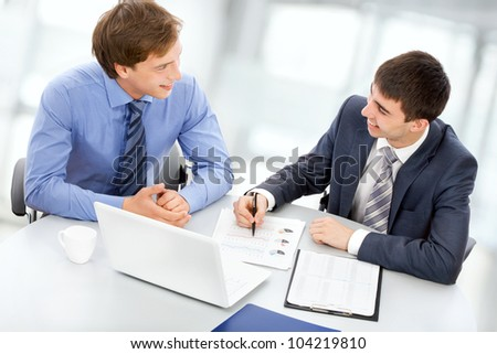 Two business men working on a laptop - stock photo