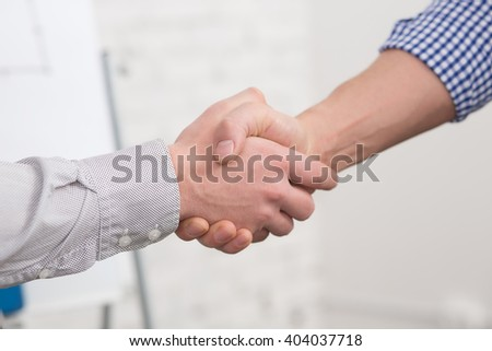 Two business partners agreed to sign contract or agreement in office. Two business people shaking hands indoors. - stock photo