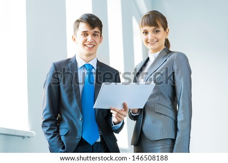 two business partners discussing documents in a bright office