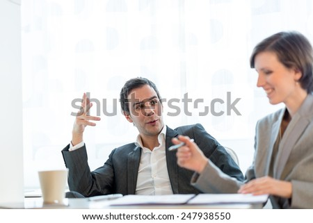 Two business partners having a meeting with a young professional man and woman in stylish clothes sitting at a desk discussing paperwork together. - stock photo
