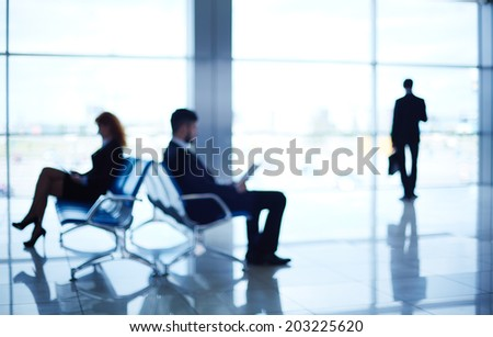 Two business partners reading at the airport while their colleague standing by the window - stock photo