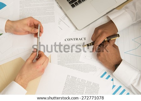 Two business partners signing a document. - stock photo