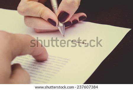 Two business partners signing a document. Toned. - stock photo