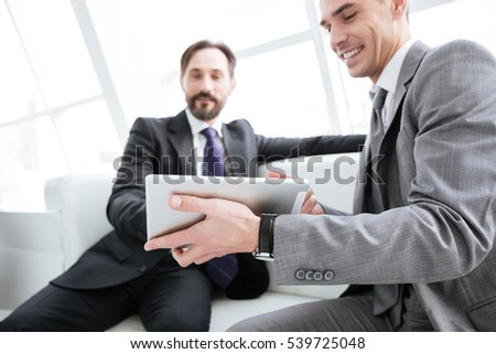 Two business partners sitting and talking with tablet computer on sofa in office. From below image