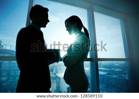 Two business partners standing by the window in office and interacting - stock photo