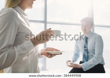 Two business partners talking while drinking coffee in office, the girl in the foreground - stock photo