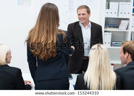 Two business people, a man and woman, shaking hands across a table in a meeting sealing an agreement or business deal - stock photo