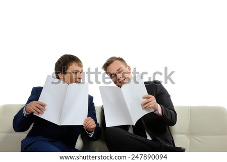 Two business people analyze the current business situation and plans for the future. There may be knowledge-sharing context as well.  Copy space on the magazines or above is for your text.  - stock photo