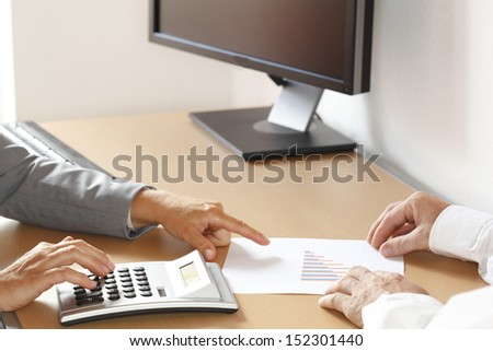 two business people are calculating in office - stock photo