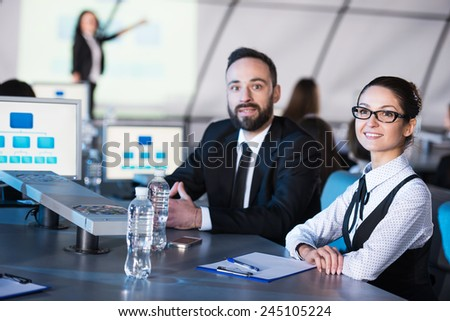 Two business people are looking at the camera during a presentation in modern conference hall. - stock photo