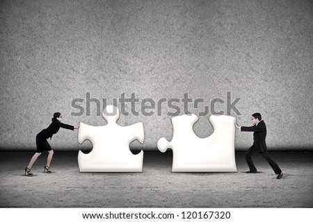 Two business people are working together to put two puzzles in order to succeed - stock photo