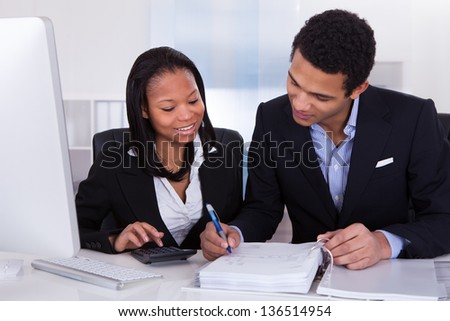 Two Business People Calculating Finance Together In Office