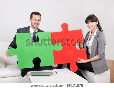 Two business people connecting puzzle pieces at the office. Teamwork concept - stock photo